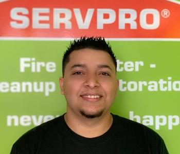 Male employee in black Servpro logo'd t-shirt standing in front of SERVPRO signage