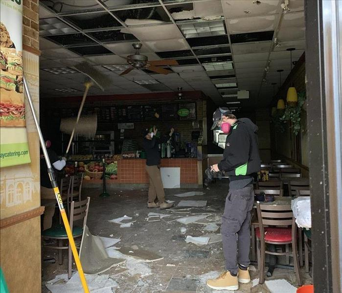 three SERVPRO workers inside fire damaged restaurant with cleaning tools