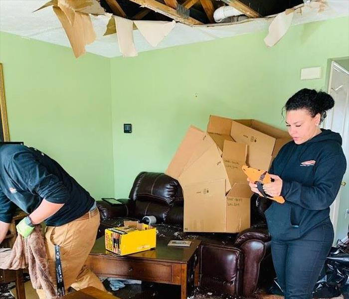 two Servpro workers reviewing restoration plans and cleaning water damaged ceiling debris