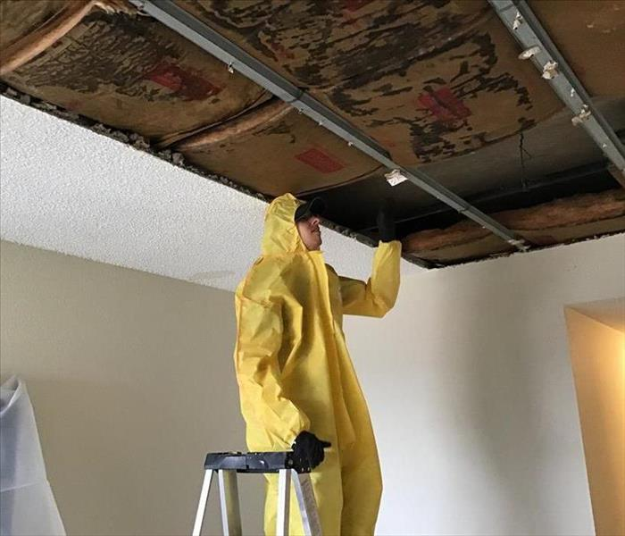 man in yellow hazmat suit standing on ladder accessing water damage to ceiling
