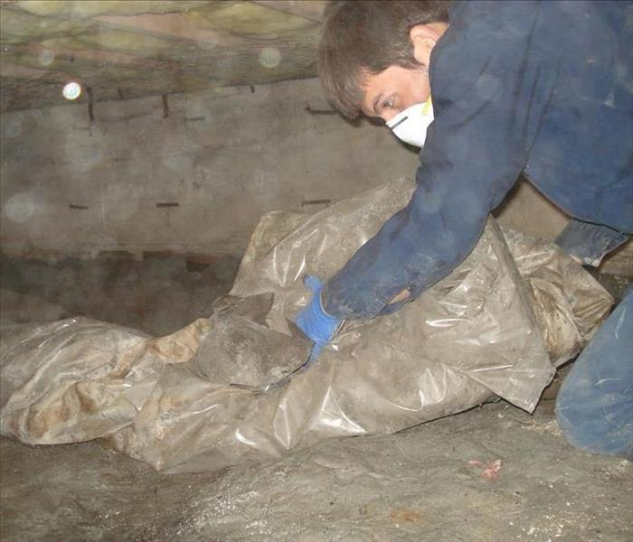 Man with blue overalls and safety mask on in crawl space rolling up plastic drop cloth