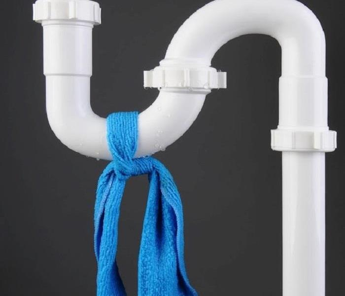 White plastic plumbing pipes with blue towel tied around piping