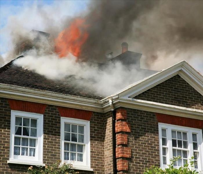 Brick house with flames and white smoke coming out of burning roof